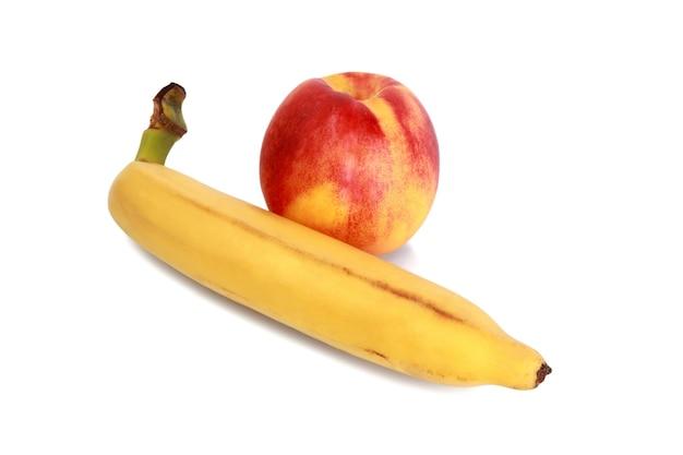 Желтый спелый банан и свежий красный персик, изолированные на белом фоне