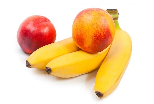 Желтый спелый банан и свежий красный персик, изолированные на белом