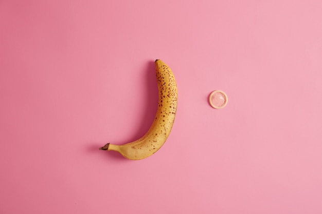 Yellow ripe banana and condom on pink background. contraception and safety.