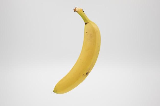 Желтый спелый банан на белом фоне