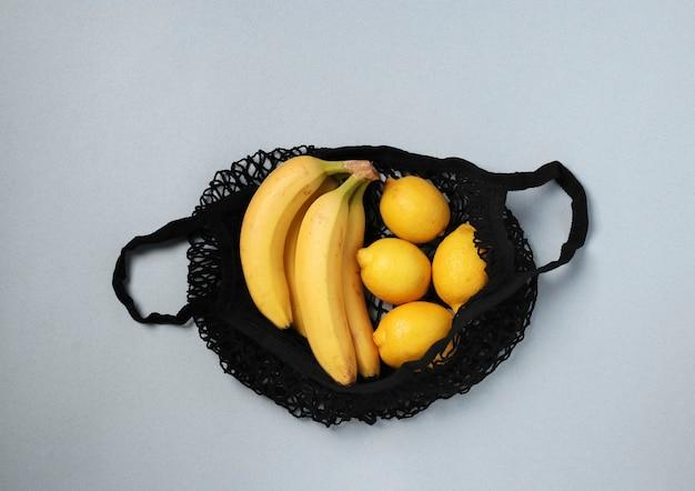 노란색 잘 익은 바나나와 레몬 밝은 배경에 검은 문자열 메쉬 가방, 제로 폐기물 개념, 위에서보기
