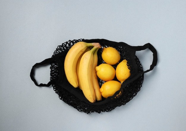 Yellow ripe bananas and lemons in black string mesh bag on light background, zero waste concept, view from above