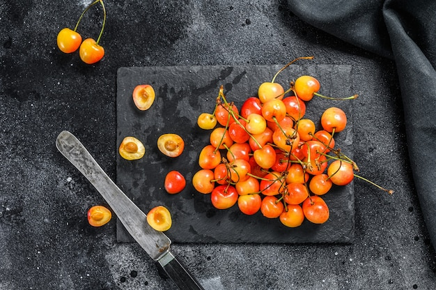 Yellow ripe cherries on a black plate. black background. top view.
