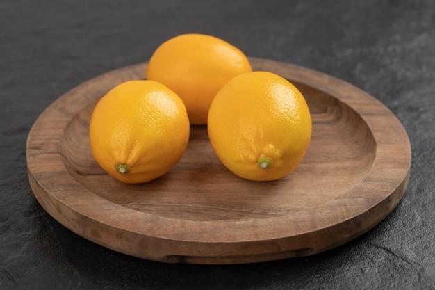 木の板の上に置かれた黄色の熟した新鮮なレモン。