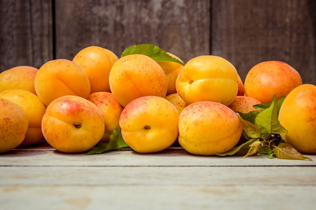 Yellow ripe juicy apricots on wooden background. selective focus.