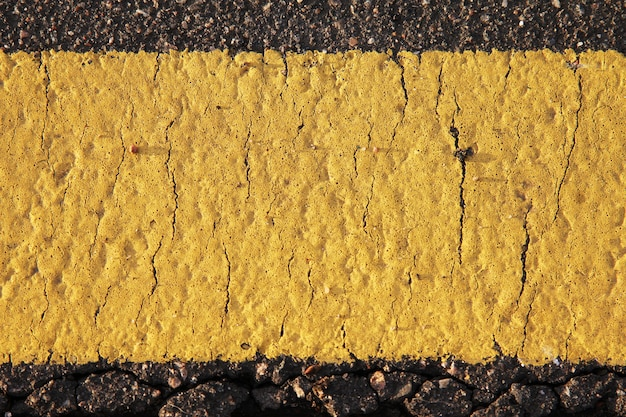 黄色の道路マークのテクスチャをクローズアップ