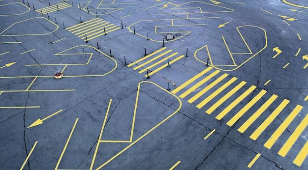 Yellow road marking on empty gray asphalt parking lot