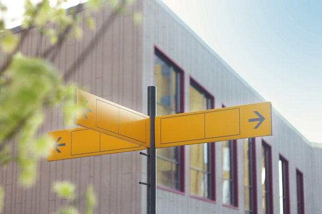 Yellow road sign or blank road signs showing direction against a building.