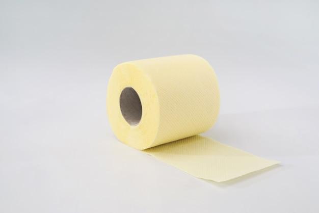 Желтый рулон туалетной бумаги на белом фоне.