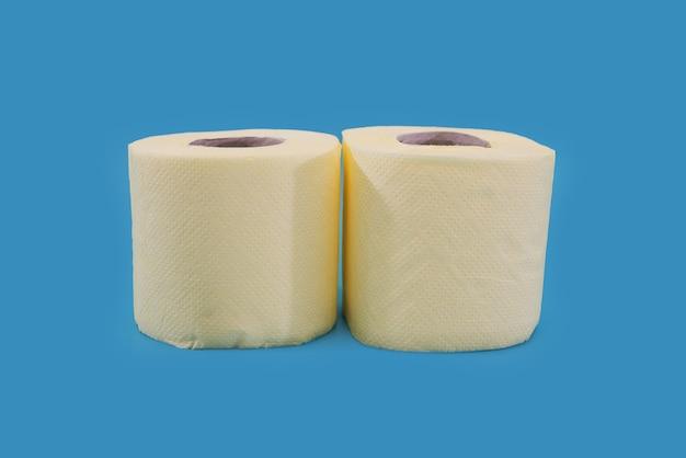 Желтые рулоны туалетной бумаги на синем фоне.