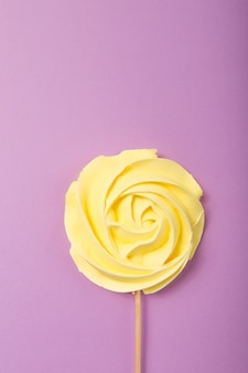 Yellow rose candy   in pastel colors on a wooden stick on a grey  background