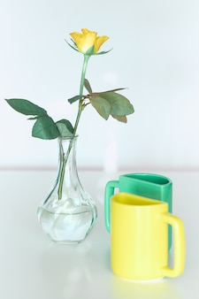 Yellow rose flower, twin half tea mugs in yellow and vibrant mint green. minimalist design for your house in bold colors. modern interior decor, romantic gifts. design for greeting card or poster.