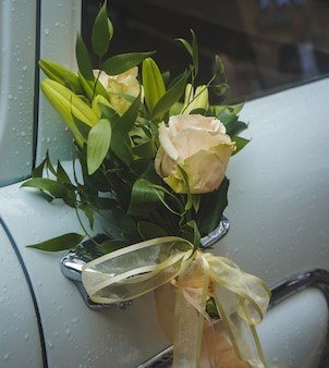 A yellow rose with decorative flowers in the handle of a white luxury car