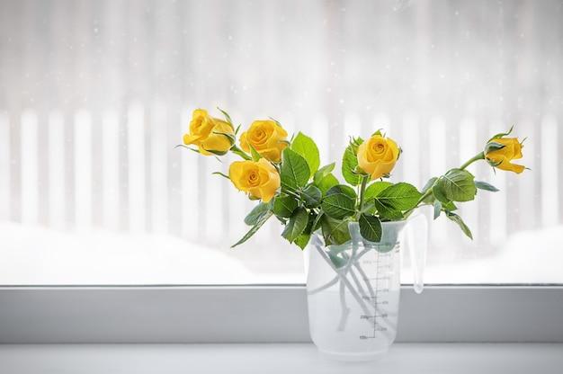 黄色いバラは窓際の花瓶にあります
