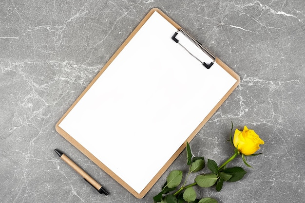 Yellow roses in craft paper and clipboard folder on gray