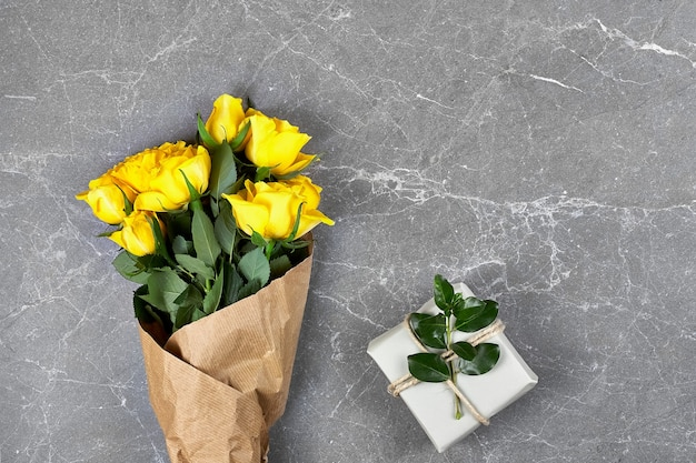 Yellow roses in craft paper and trendy gift box in recycled paper on gray