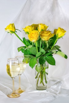 Yellow roses and glasses of wine on a white background with chiffon drape
