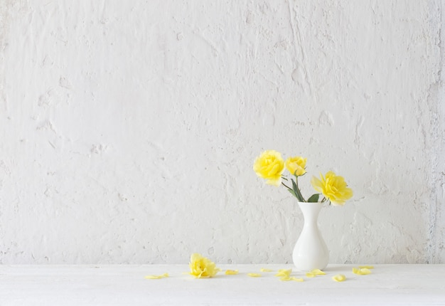 Желтые розы в белой вазе на фоне белой стены