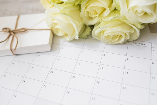 Yellow roses and stack of envelopes on calendar