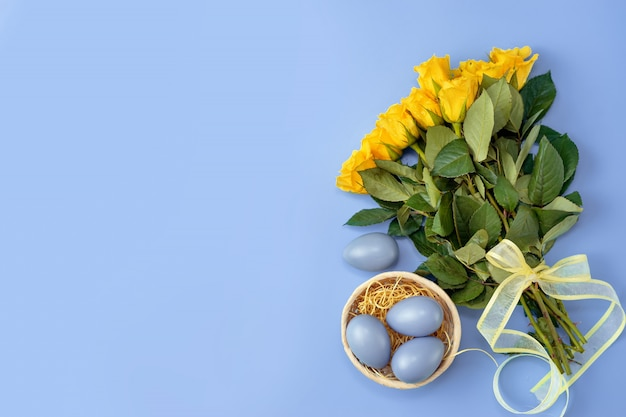 Yellow roses with blue easter eggs on trendy colorful background