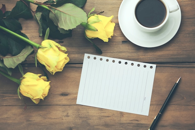 Yellow roses with page and coffee