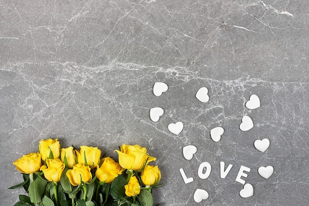 Yellow roses, word love and white hearts on gray