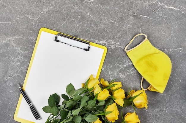 Yellow roses, yellow protective mask and clipboard folder on gray