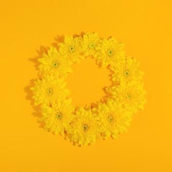 コピースペースと明るい黄色の背景上面図レイアウトに菊の花と黄色の丸いフレームの表面