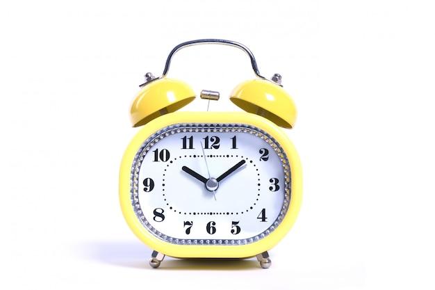 Yellow round oldfashioned glossy retro alarm clock isolated on white close up