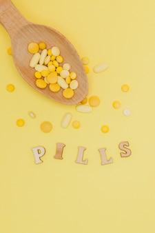 Желтые круглые витаминные таблетки в ложке на желтом фоне