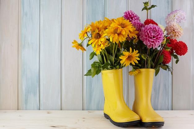 먼지와 꽃이 들어있는 노란색 고무 장화