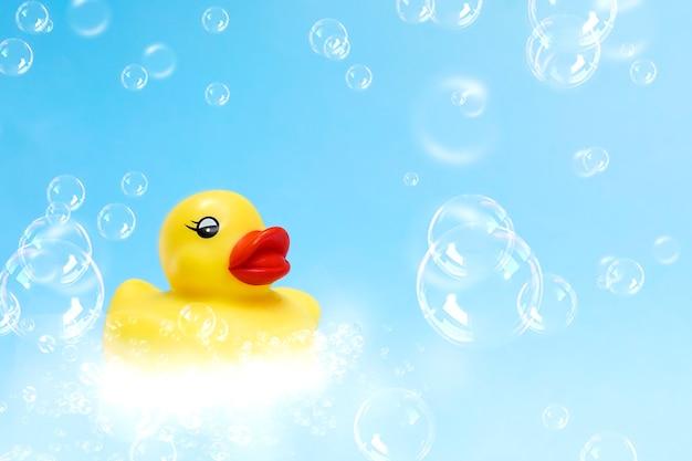 Желтая резиновая утка на голубой поверхности с мыльными пузырями