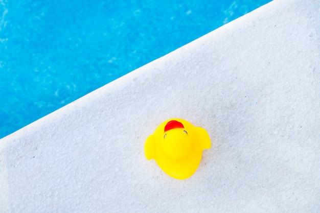 Желтая резиновая утка на краю бассейна