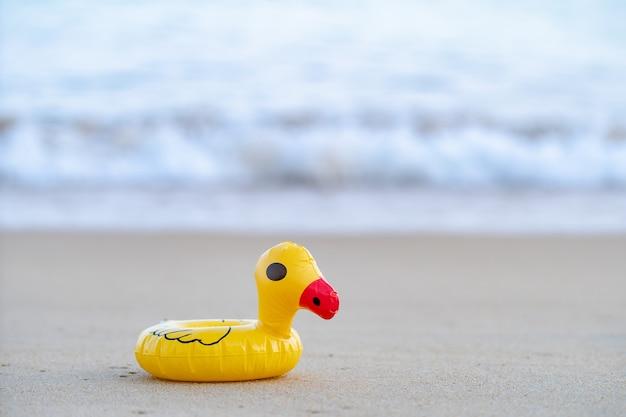 Желтая резиновая утка на берегу моря утром, песчаный пляж.