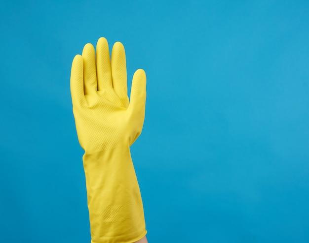 Желтая резиновая перчатка для уборки одета на женскую руку, синий фон