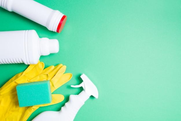 노란색 고무 장갑, 세척 용 녹색 스폰지 및 녹색 표면에 세제 용 라벨이없는 여러 종류의 흰색 플라스틱 병