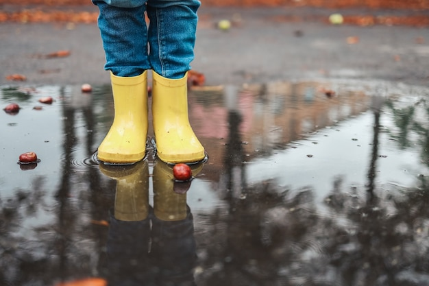 Yellow rubber shoes in puddle after raining. falling leaves. autumn season concept.