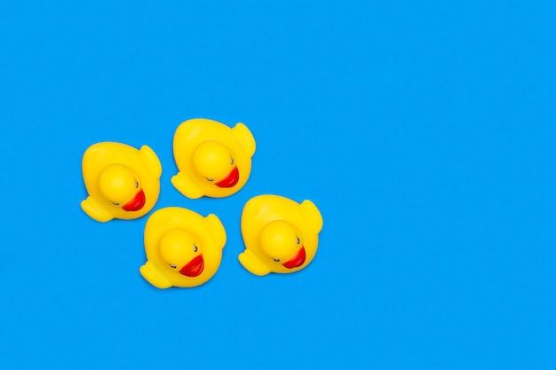 Желтые резиновые игрушечные утки, изолированные на синем