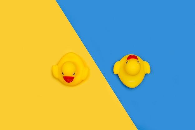 Желтые резиновые игрушечные утки, изолированные на желтом и синем