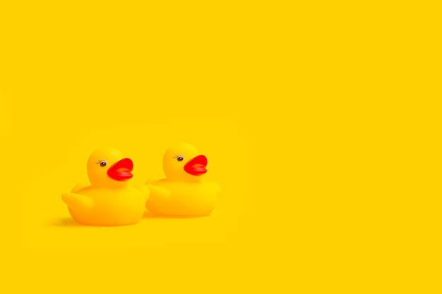 Желтые резиновые игрушечные утки, изолированные на желтом