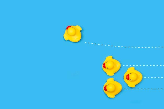青地に白の破線の黄色いゴム製のおもちゃのアヒル