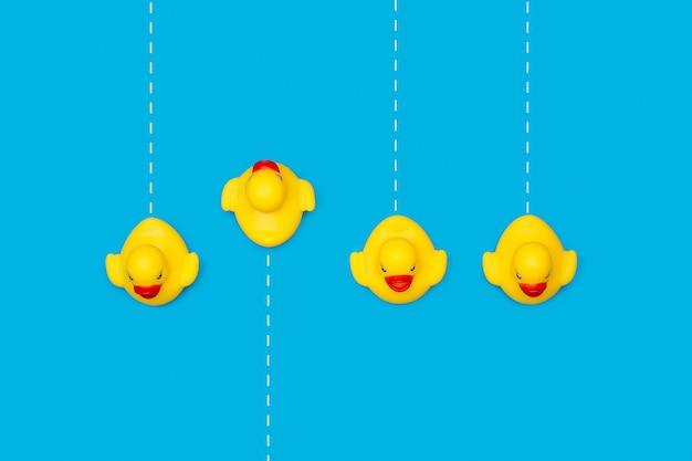 Желтые резиновые игрушечные утки на синем с пунктирными белыми линиями