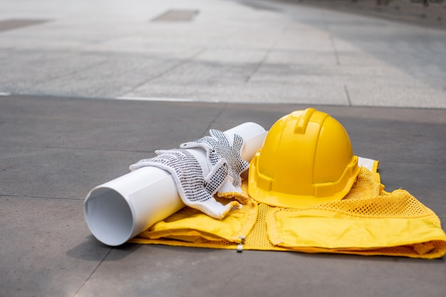 Yellow safety helmet with glove, blueprint on vest on floor