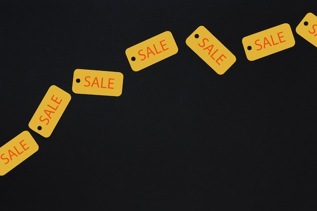Yellow sale tags on dark background