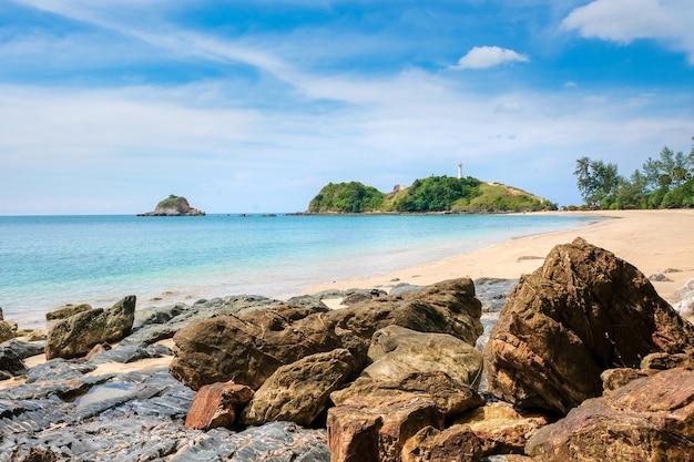 黄色い砂と大きな石、ターコイズブルーの海と空、崖の上の白い灯台
