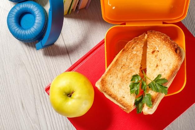 トーストしたパン、チーズ、緑のパセリ、青リンゴ、ヘッドフォン、ハードカバーの本が背景にある黄色のサンドイッチボックス。学校の朝食。