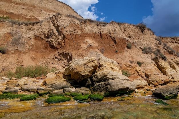 흑해 연안의 황사암과 다양한 형태의 돌. 푸른 하늘과 청록색 물.