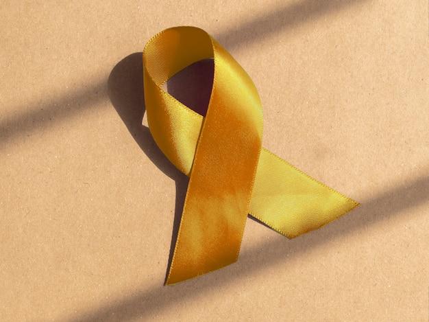Желтая атласная лента в виде медицинской символической петли