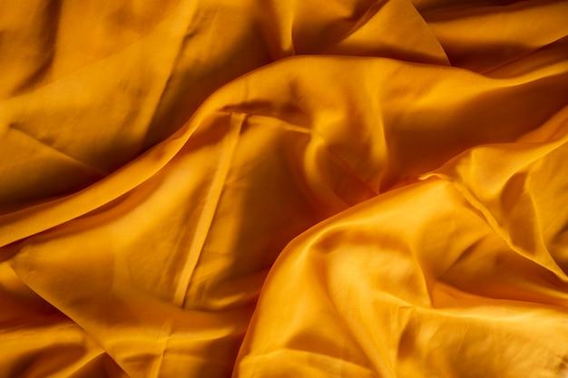 黄色のスカーフ生地のテクスチャの背景。ミニマリストのコンセプト