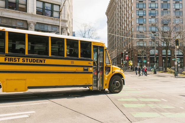 Yellow school bus rides on the city road